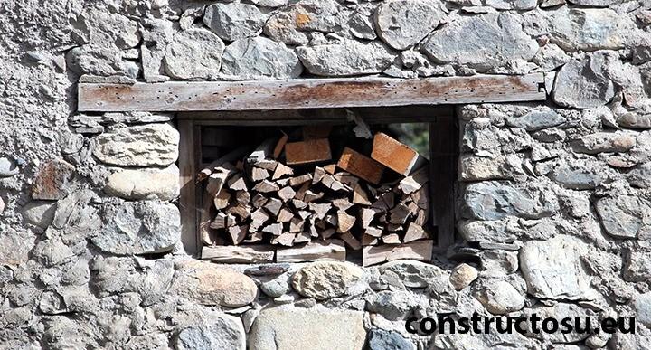 Fereastră mică în perete de piatră cu buiandrug de lemn