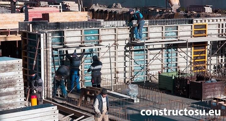 Muncitori și constructori pe șantier pe timp friguros